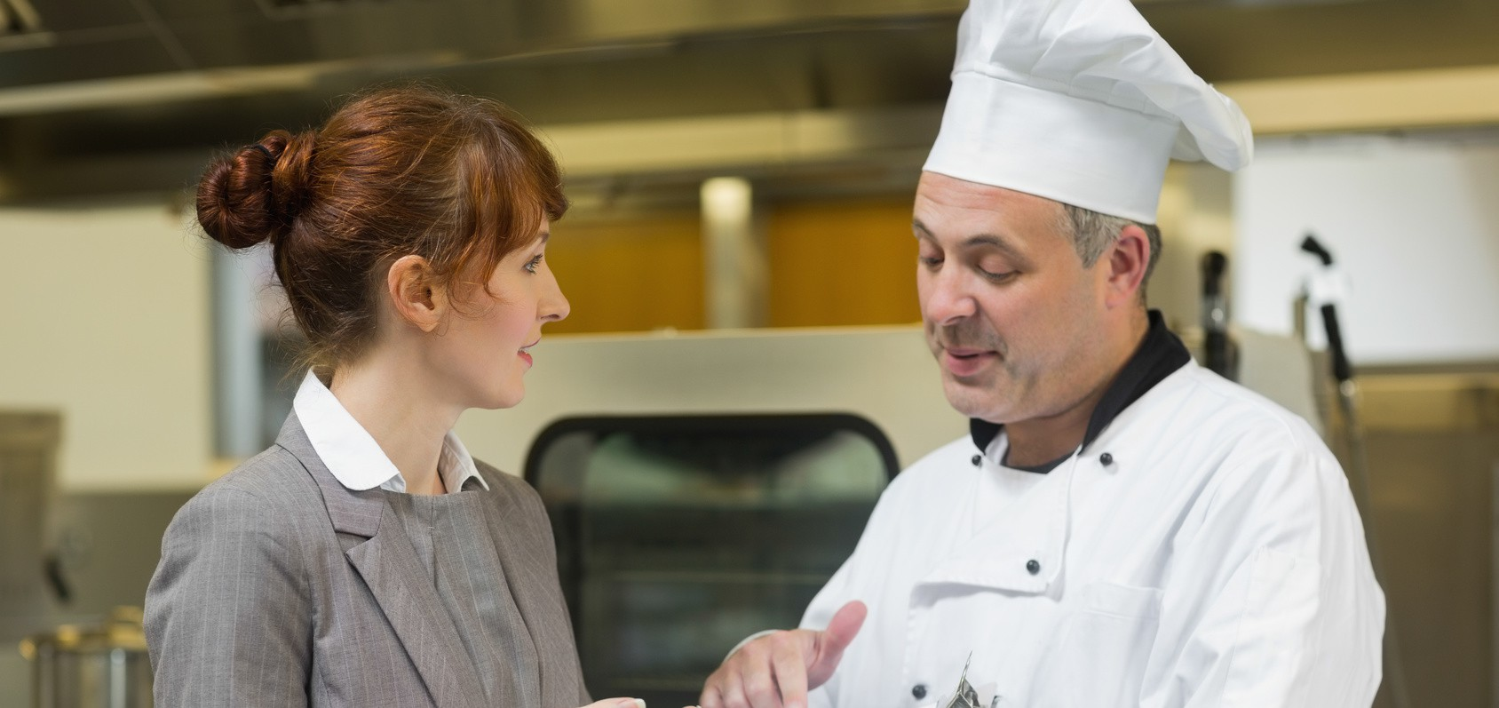 Young female manager talking to the head cook standing in a professional kitchen
